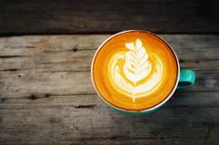 Café de cappuccino dans une tasse verte sur en bois Image libre de droits