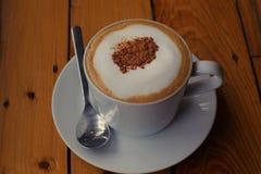 Café de Cappuchino dans la tasse et soucoupe porcellan blanche avec la cuillère et la cannelle étroites Photos stock