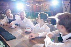 Café de charla y de consumición del personal alegre del restaurante después del wor imagenes de archivo