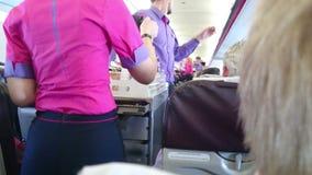 Café de colada del uniforme del asistente de la mujer en vuelo para el pasajero a bordo del avión metrajes