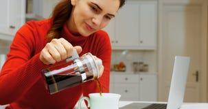 Café de colada de la mujer en la taza en la cocina 4k almacen de metraje de vídeo