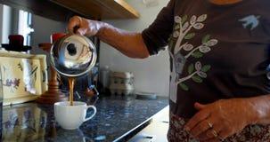 Café de colada de la mujer mayor en la taza de café en la cocina 4k metrajes