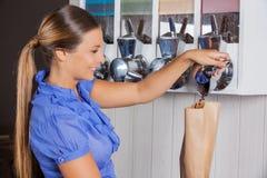 Café de compra de la mujer de la máquina expendedora adentro Fotos de archivo libres de regalías
