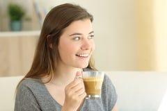 Café de consumición adolescente feliz con la leche que mira el lado Foto de archivo libre de regalías