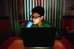 Café de consumición adolescente joven delante de un ordenador portátil Fotos de archivo