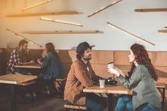 Café de consumición alegre del hombre joven y de la mujer en café Fotos de archivo libres de regalías
