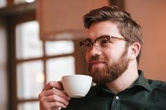 Café de consumición barbudo sonriente del hombre joven Foto de archivo