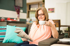 Café de consumición de la abuela mientras que lee Fotos de archivo libres de regalías