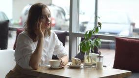 Café de consumición de la chica joven y el hablar en el teléfono móvil en café Mujer de negocios en hora de la almuerzo almacen de metraje de vídeo