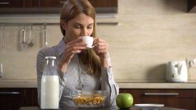 Café de consumición de la empresaria atractiva joven hermosa Comer copos de maíz para el desayuno almacen de video