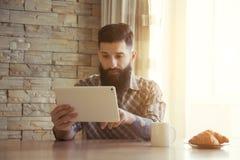Café de consumición de la mañana del hombre con la tableta Fotos de archivo