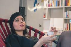 Café de consumición de la morenita joven hermosa en una librería Fotografía de archivo libre de regalías