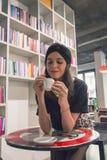 Café de consumición de la morenita joven hermosa en una librería Fotografía de archivo