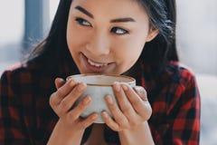 Café de consumición de la muchacha asiática en el café, concepto del descanso para tomar café Fotografía de archivo