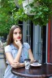 Café de consumición de la muchacha atractiva joven con el mollete en el caf al aire libre Fotos de archivo