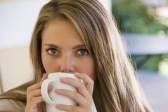 Café de consumición de la muchacha de una taza Imagenes de archivo