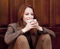 Café de consumición de la muchacha del redhead del estilo Fotos de archivo libres de regalías
