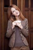 Café de consumición de la muchacha del redhead del estilo Foto de archivo libre de regalías