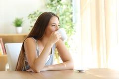 Café de consumición de la muchacha en casa Foto de archivo libre de regalías
