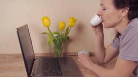 Café de consumición de la muchacha en la cocina En la tabla de cocina al lado de la muchacha del ordenador portátil que bebe el c almacen de metraje de vídeo