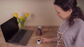 Café de consumición de la muchacha en la cocina En la tabla de cocina al lado de la muchacha del ordenador portátil que bebe el c metrajes