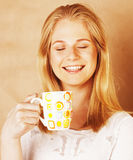 Café de consumición de la muchacha rubia linda joven cercano para arriba en el CCB caliente del marrón Imagenes de archivo