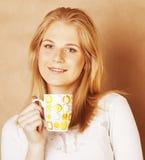 Café de consumición de la muchacha rubia linda joven cercano para arriba en el CCB caliente del marrón Imagen de archivo