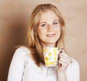 Café de consumición de la muchacha rubia linda joven cercano para arriba en el CCB caliente del marrón Imágenes de archivo libres de regalías