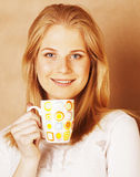 Café de consumición de la muchacha rubia linda joven cercano para arriba en el CCB caliente del marrón Foto de archivo