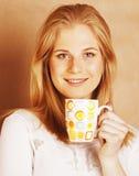 Café de consumición de la muchacha rubia linda joven cercano para arriba en el CCB caliente del marrón Fotos de archivo