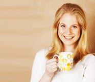 Café de consumición de la muchacha rubia linda joven cercano para arriba en el CCB caliente del marrón Imagen de archivo libre de regalías