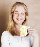 Café de consumición de la muchacha rubia linda joven cercano para arriba en el CCB caliente del marrón Fotografía de archivo