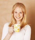 Café de consumición de la muchacha rubia linda joven cercano para arriba en fondo marrón caliente Foto de archivo