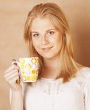 Café de consumición de la muchacha rubia linda joven cercano para arriba en fondo marrón caliente Imagen de archivo libre de regalías
