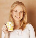 Café de consumición de la muchacha rubia linda joven cercano para arriba en fondo marrón caliente Fotos de archivo