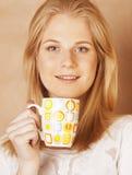 Café de consumición de la muchacha rubia linda joven cercano para arriba en fondo marrón caliente Imagen de archivo