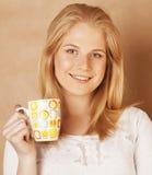 Café de consumición de la muchacha rubia linda joven cercano para arriba en fondo marrón caliente Fotografía de archivo