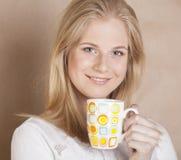 Café de consumición de la muchacha rubia linda joven cercano para arriba encendido Imagen de archivo