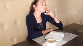 Café de consumición de la muchacha y el hablar en el teléfono metrajes