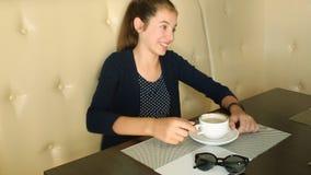 Café de consumición de la muchacha y el hablar en el teléfono almacen de video