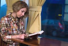 Café de consumición de la muchacha y lectura de un libro. Fotos de archivo