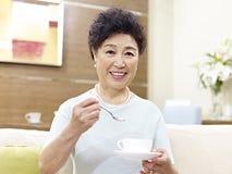 Café de consumición de la mujer asiática mayor Foto de archivo libre de regalías