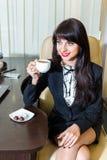 Café de consumición de la mujer atractiva en la oficina Imagenes de archivo