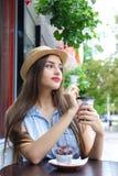 Café de consumición de la mujer atractiva joven con el mollete en el Ca al aire libre Fotos de archivo