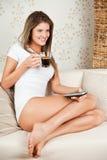 Café de consumición de la mujer atractiva joven en el sof Imágenes de archivo libres de regalías