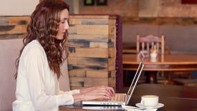 Café de consumición de la mujer bonita mientras que usa el ordenador portátil almacen de video