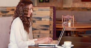 Café de consumición de la mujer bonita mientras que usa el ordenador portátil almacen de metraje de vídeo