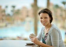 Café de consumición de la mujer cerca de la piscina fotografía de archivo