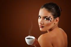 Café de consumición de la mujer con maquillaje hermoso aislado en marrón Fotografía de archivo