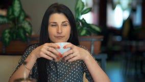 Café de consumición de la mujer de negocios en el café metrajes